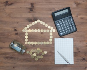 coins in house shaped, calculator pen and notebook
