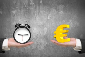 Euro symbol on one hand and alarm clock on another hand, with concrete wall background, concept of deal and time.