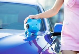 Cropped image woman customer, new car, piggy bank, key on hood