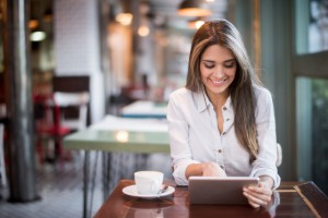 Woman using her tablet at a restaurant while drinking a cup of coffee