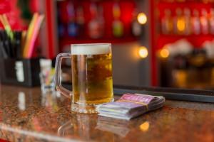 mug of beer and money on the bar