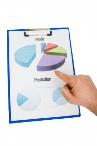 Hand pointing on colorful charts on clipboard. Profit pie chart and sales prediction concept