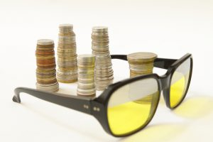 Stakes of coins and old style sunglasses