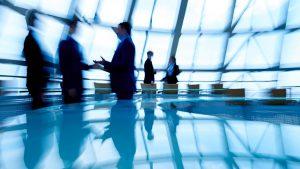 Defocused figures of business people interacting in boardroom
