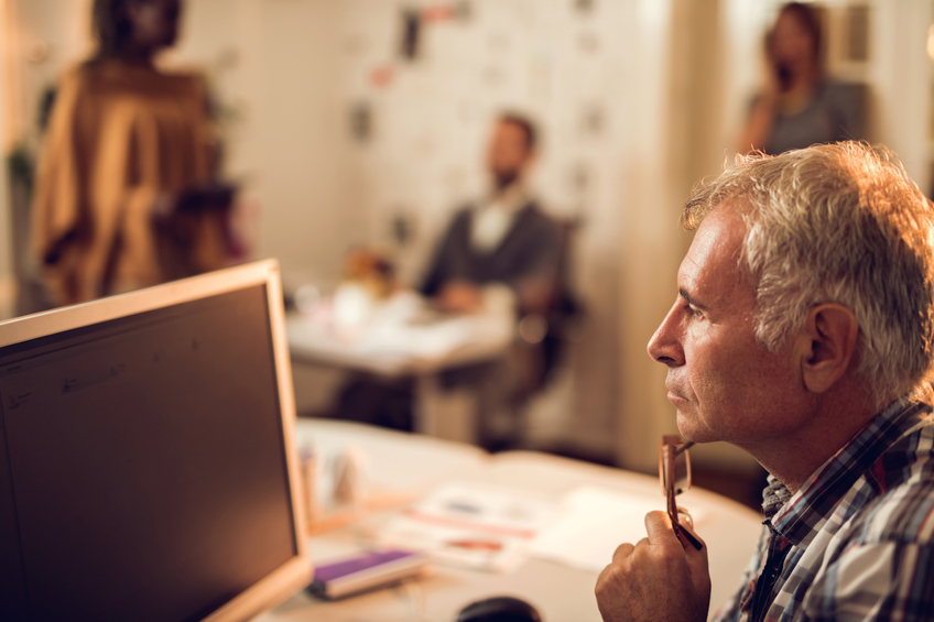 Close up of a senior businessman thinking while looking at desktop monitor in the office. There are people in the background.