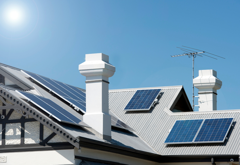 Solar panels on a house roof with sun