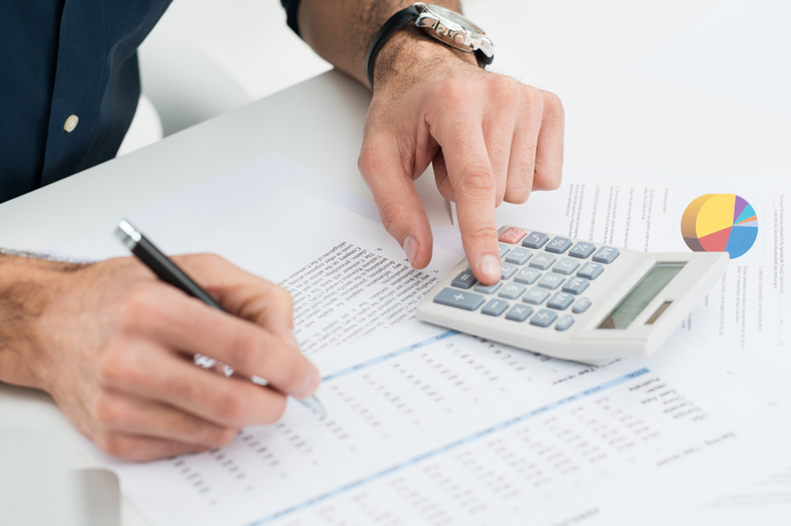 Closeup Of Man Calculating Financial Bills With Calculator