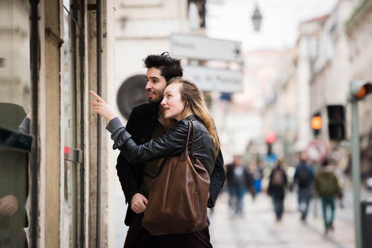 Trendy young couple window shopping together in a European city