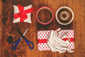 Christmas gifts and presents wrapping, assorted decorative polka dotted paper, scissors and ribbon tapes on wooden desk, top view, retro toned