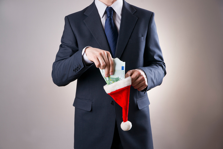 Businessman putting money in a Santa hat on gray background